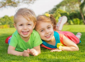 Picture of brother and sister having fun in the park, two cheerful child laying down on green grass, little girl and boy playing outdoors, best friends, happy family, love and happiness concept